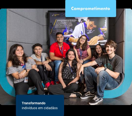 Sete jovens sentados no chão, todos de crachá, sorrindo e olhando para a câmera. Atrás deles há uma tela grande.