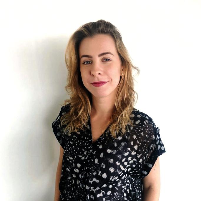 Mulher olhando para a câmera em frente a uma parede branca. Ela é branca, loira e está vestindo uma blusa de manga curta preta com detalhes brancos